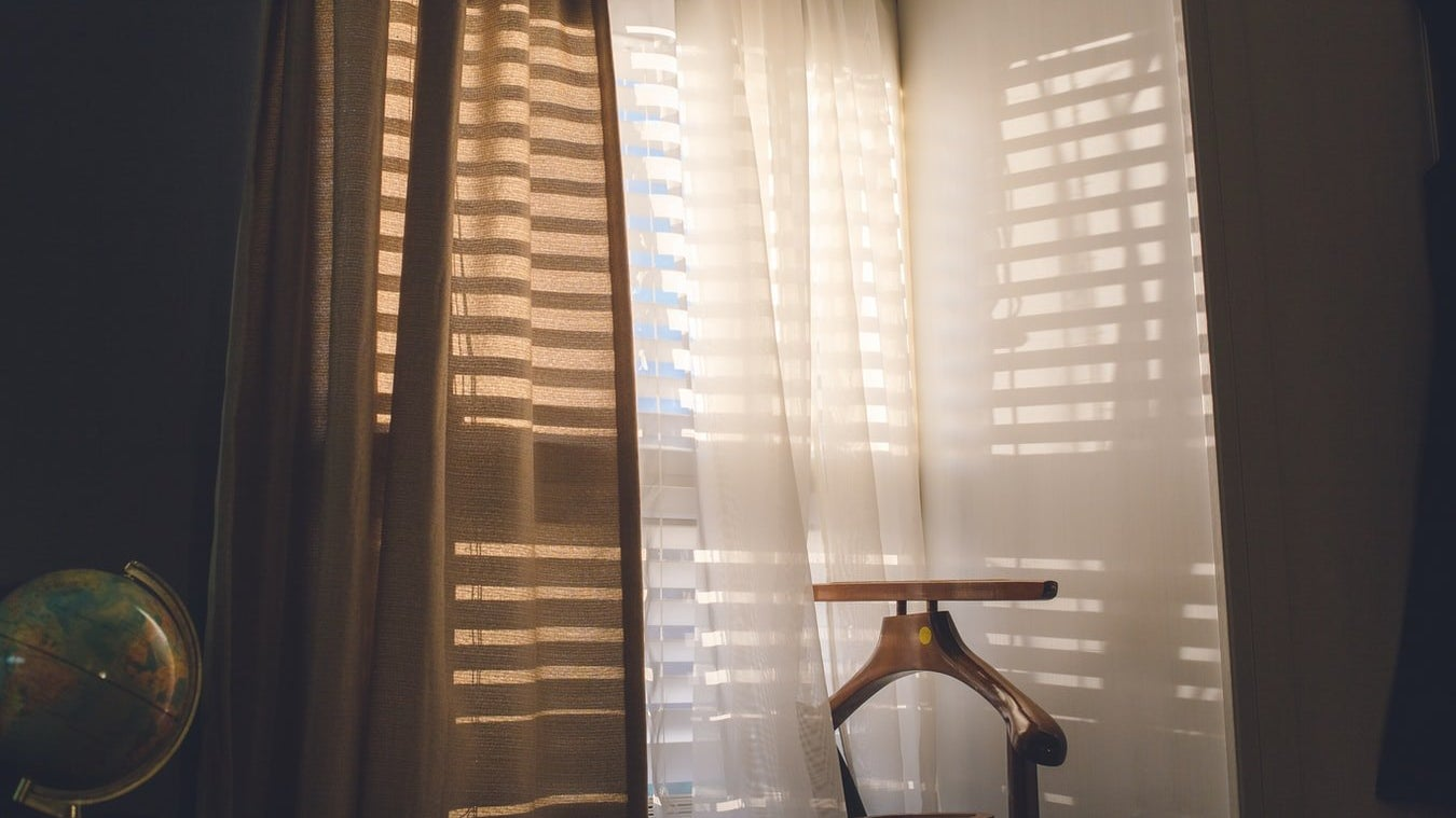 Curtains in front of blinds in a bedroom