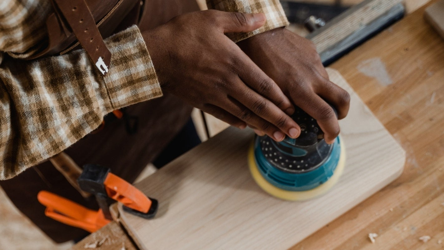 Hands using an orbital sander on a piece of small light colored wood clamped to workbench with orange clamps