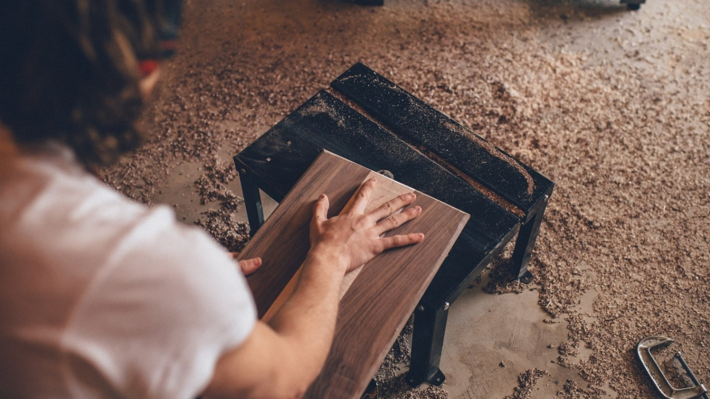 Person woodworking in a woodshop covered in saw dust, holding a cut piece of finished wood atop a small black workbench
