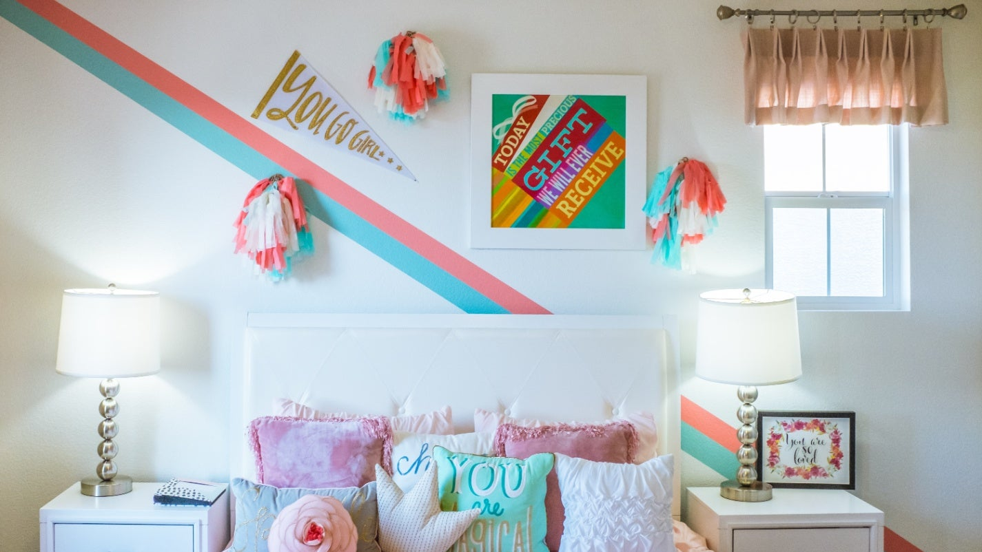Photo of bedroom that's mostly white, but with pops of bright, pastel colours.