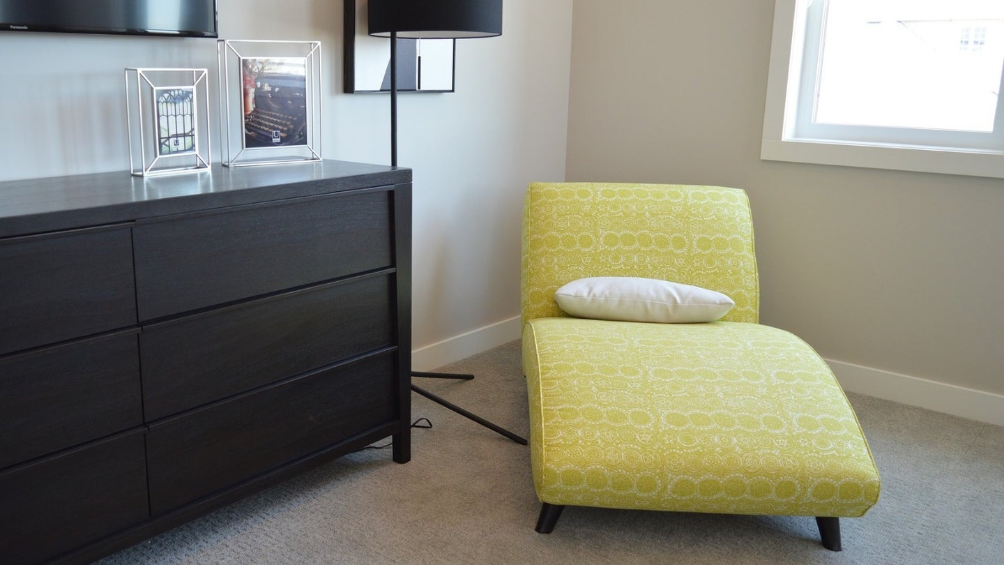 A yellow chaise in a bedroom