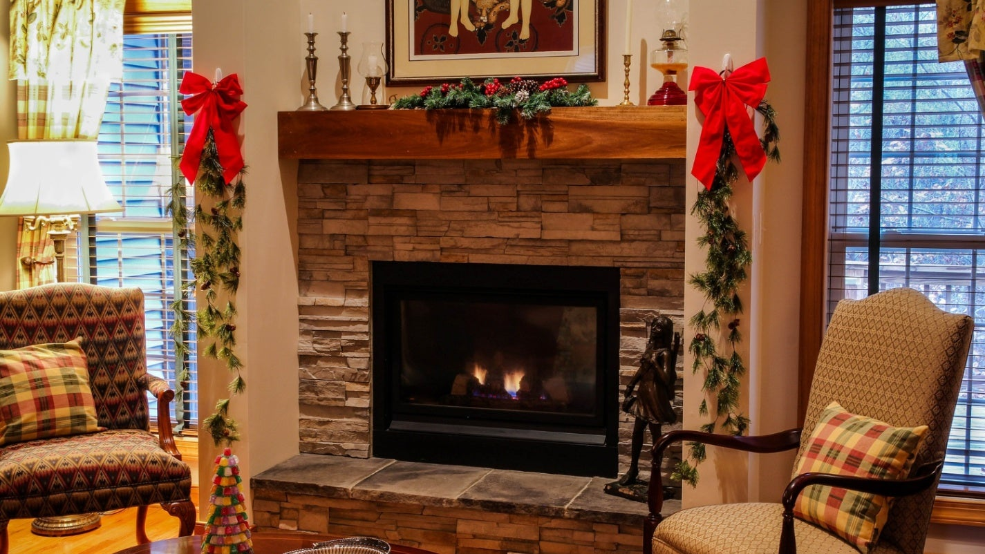 A gas fireplace in a living room decorated for Christmas