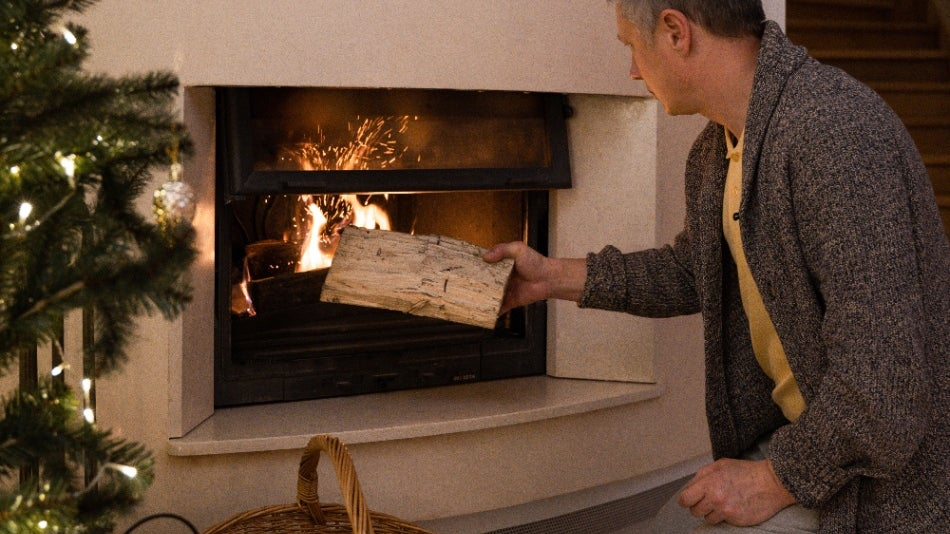 Man putting wood in fireplace at Christmas.