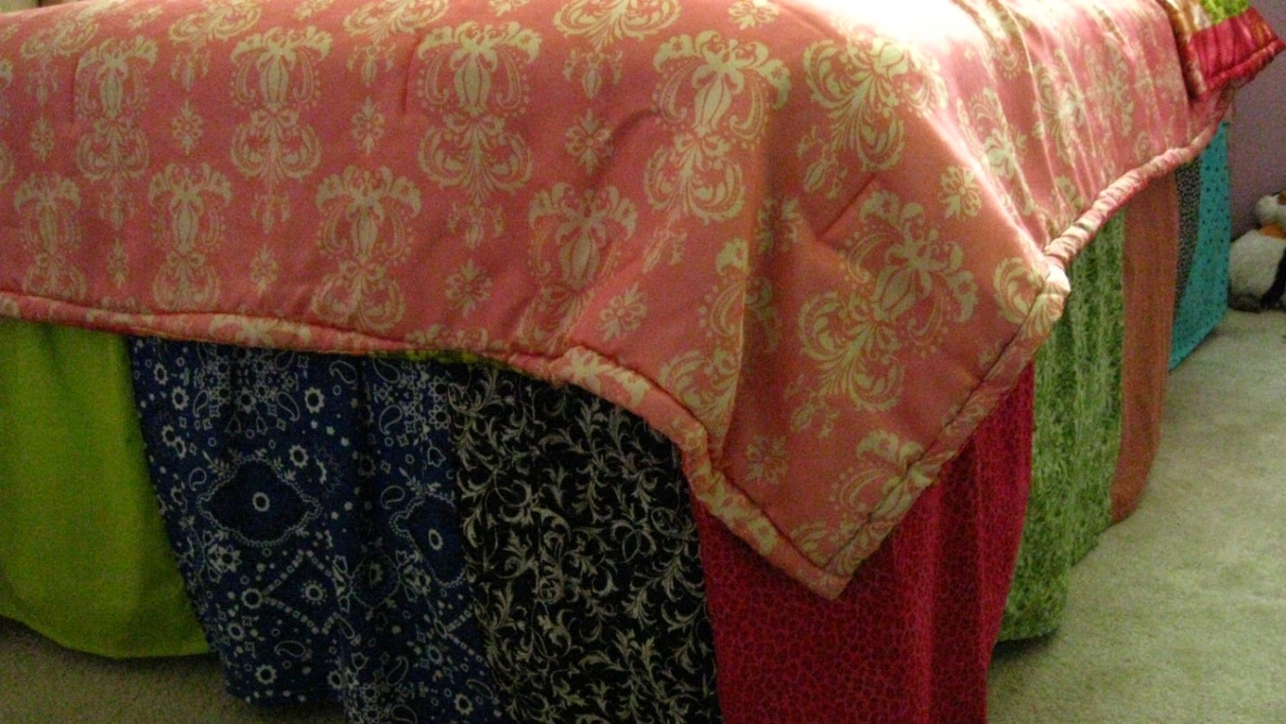 A bed skirt made with multiple bright colours of fabric.