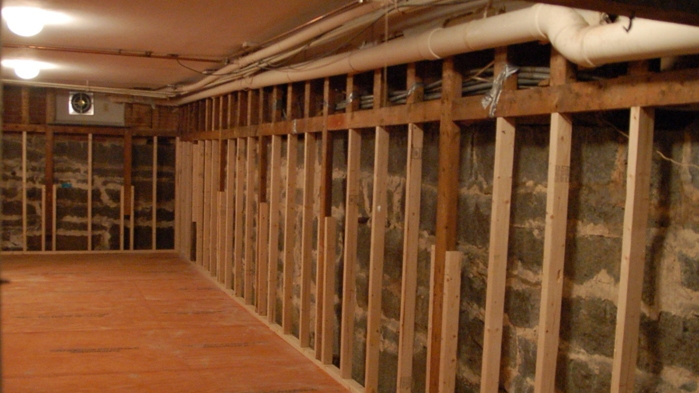 An unfinished basement with studs visible.