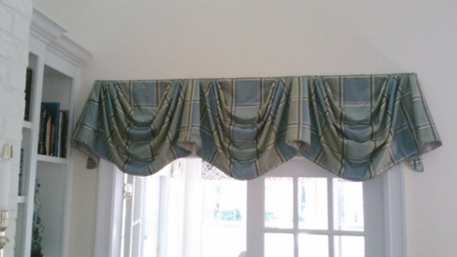 A window with a ruffled, plaid valance.