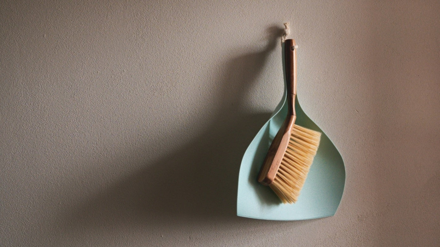 Dustpan and brush hanging on a wall.