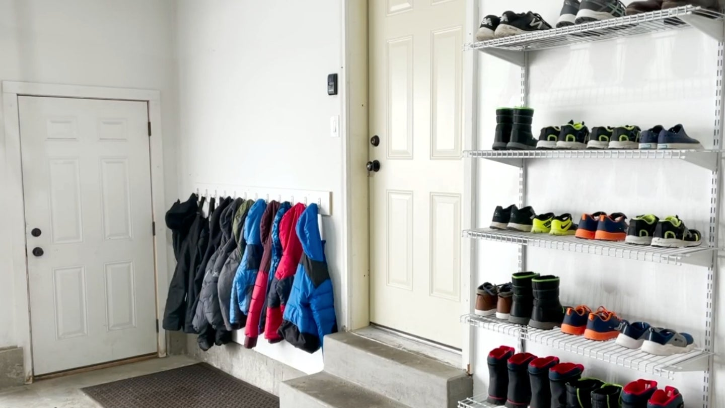 A garage with hanging metal wire shelving to store boots and shoes.