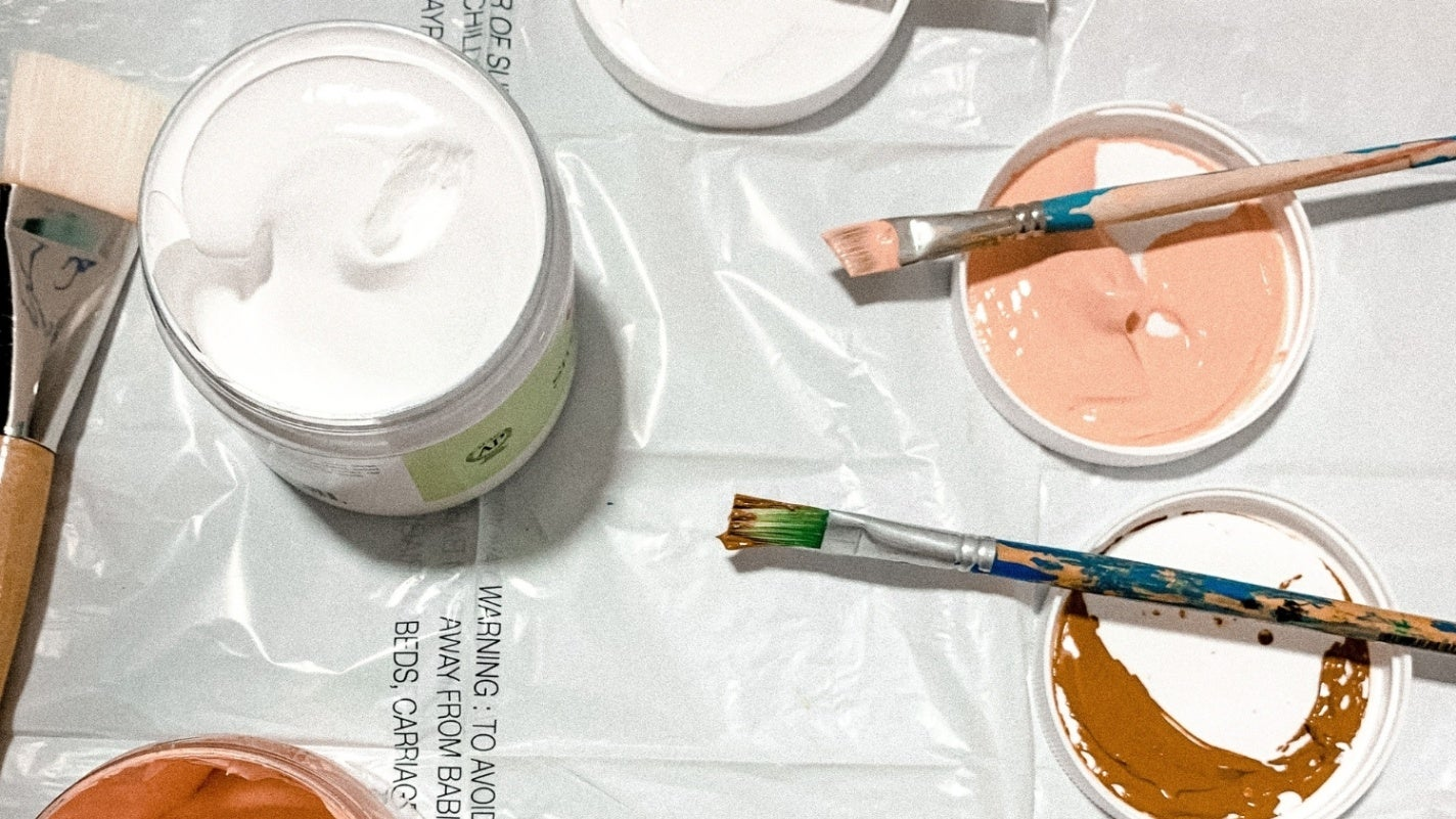 Pink and brown paint containers opened with their lids off and used brushed lying across lids on plastic sheet