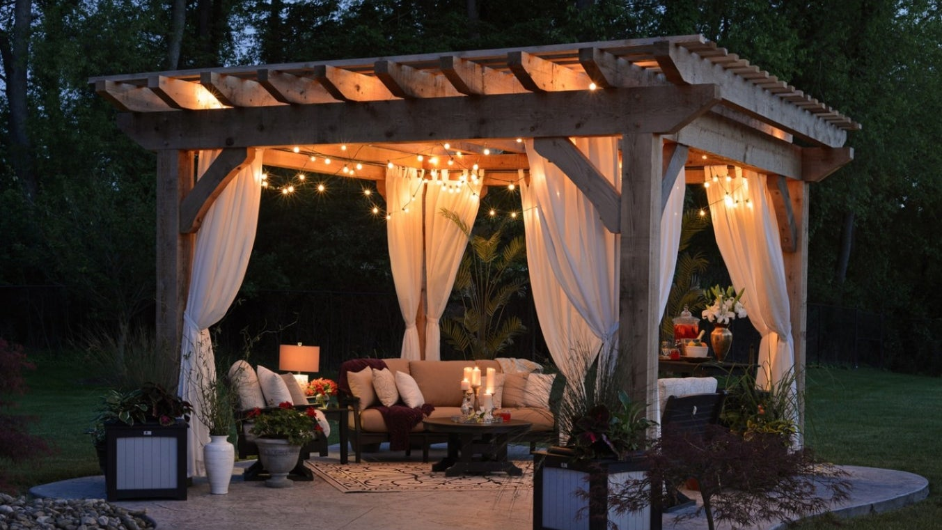 A gazebo with curtains and canopy of lights at night.