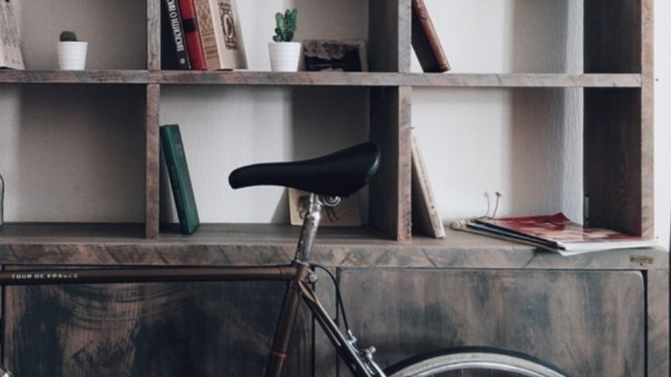 Bicycle leaning on cabinets with a bookshelf above.
