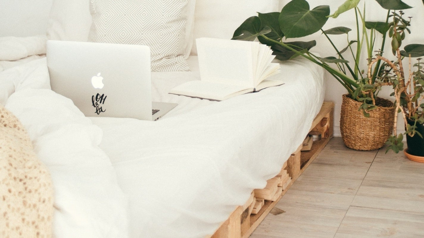 Bright bedroom with a DIY pallet bed frame that has storage underneath the mattress.