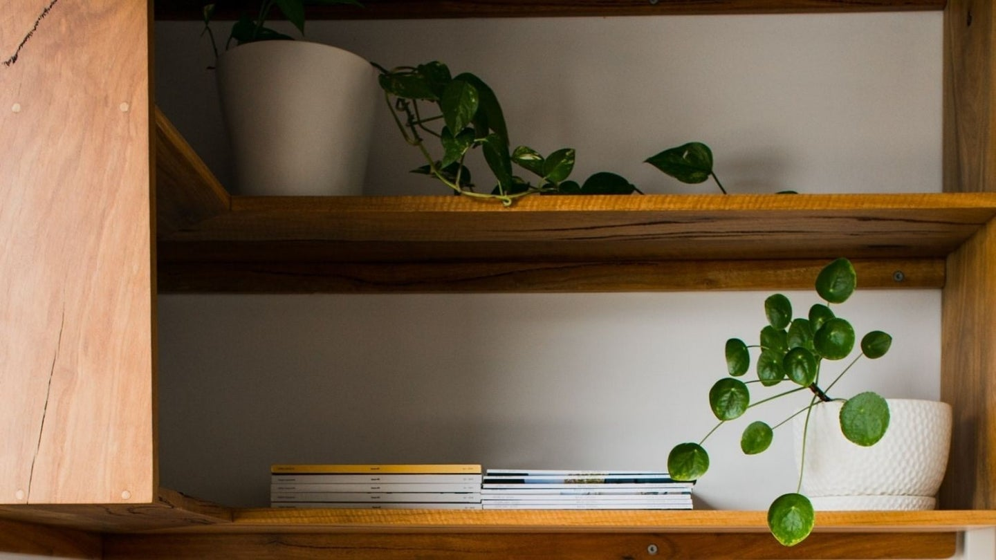 A floating corner shelf made of wood with plants, books, and magazines on it.