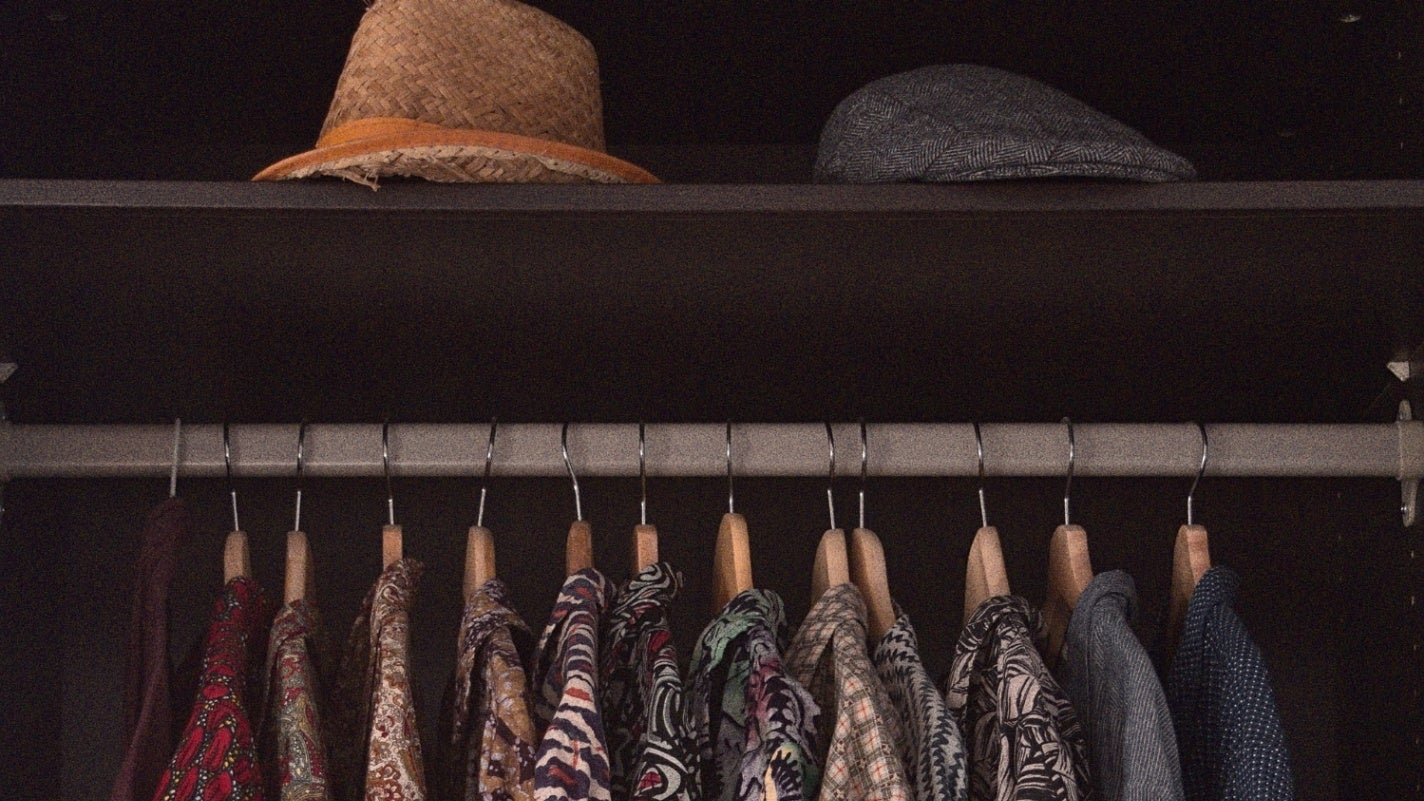 Shirts hanging on hangers in an armoire with hats on a shelf above.