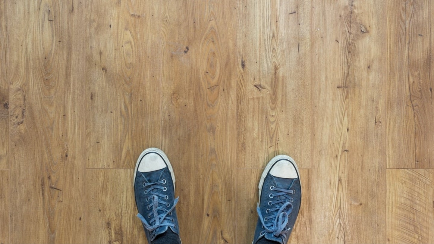 A photograph someone has taken from above of their shoes while standing on a wood floor.