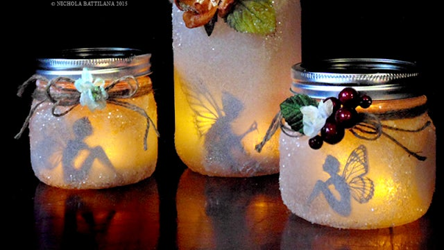 three completed fairy lanterns, lit and glowing with fairy cutouts inside