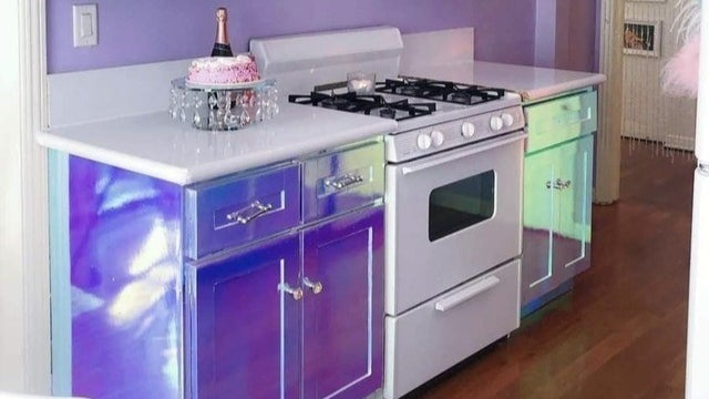 A kitchen with shiny, reflective, iridescent cupboards.