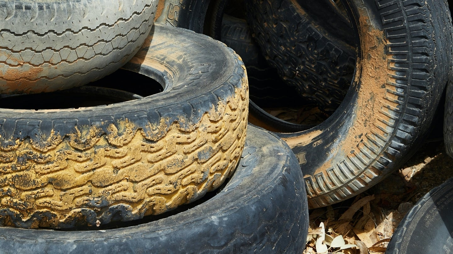 old muddy tires in a pile