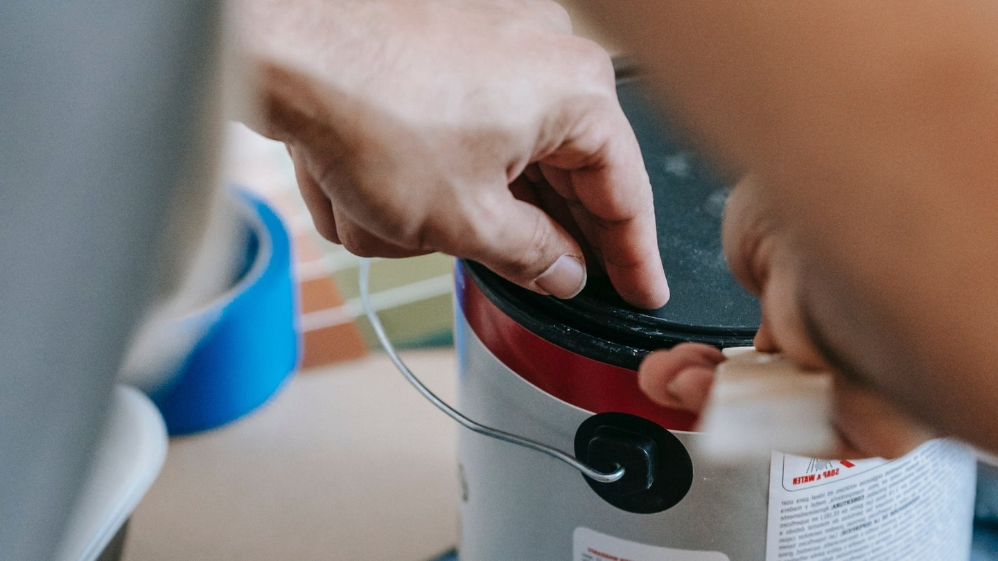 hands opening a paint can