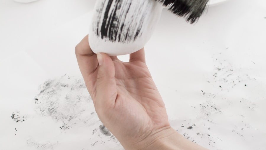 A person painting a white clay bowl with streaks of black paint.