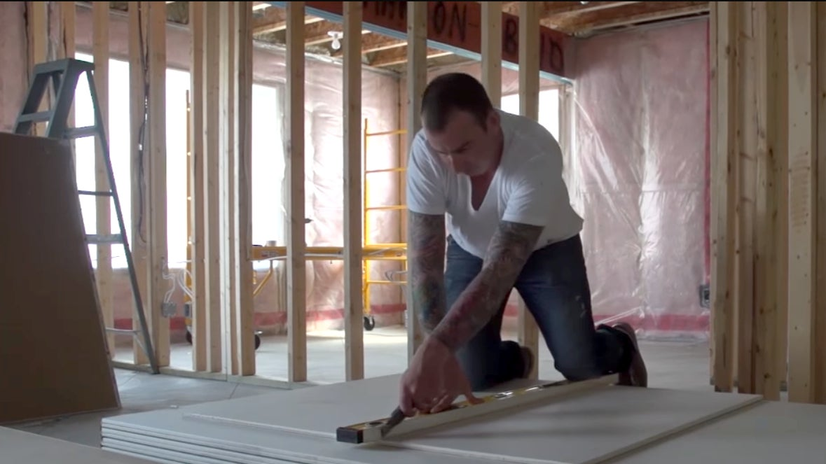 A man cuts a large sheet of drywall with a utility knife and uses a level as a straight edge.