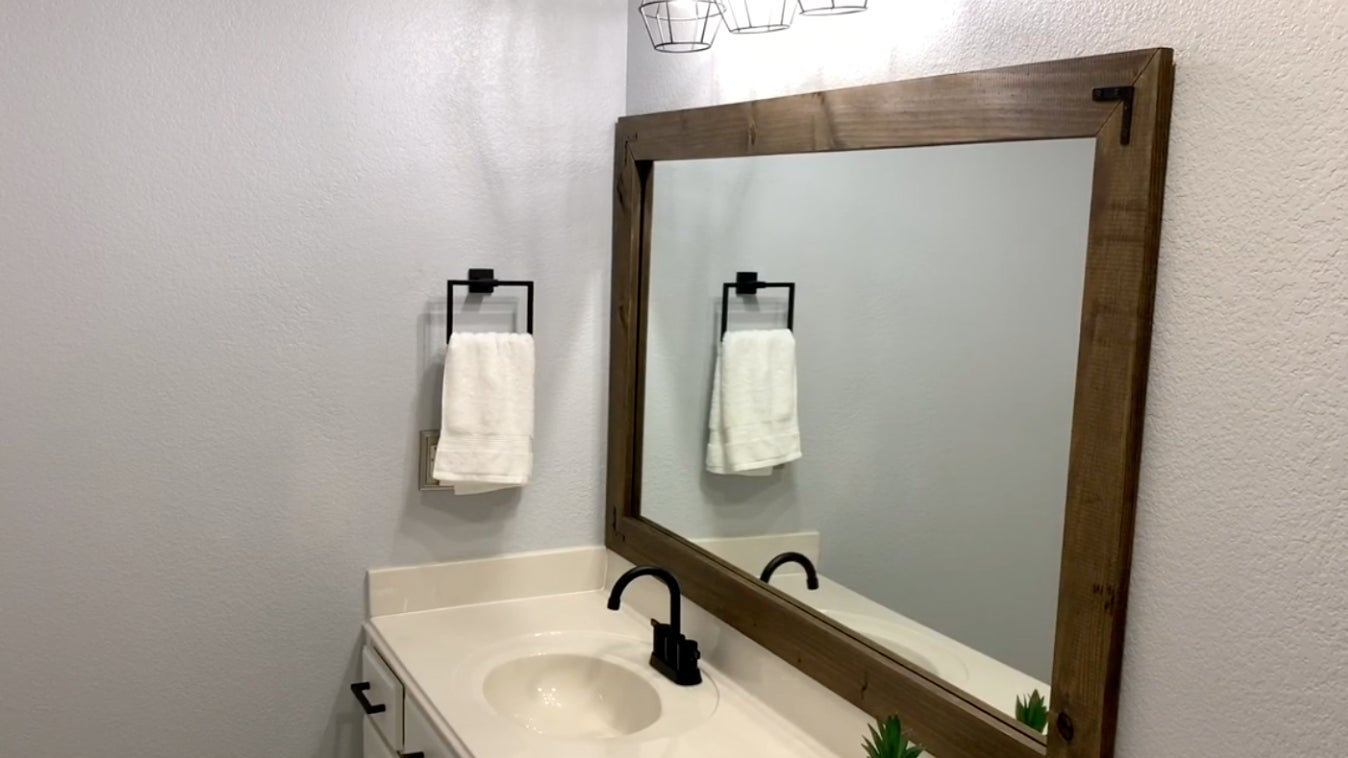 Bathroom vanity with a framed wooden mirror on the wall above the sink.