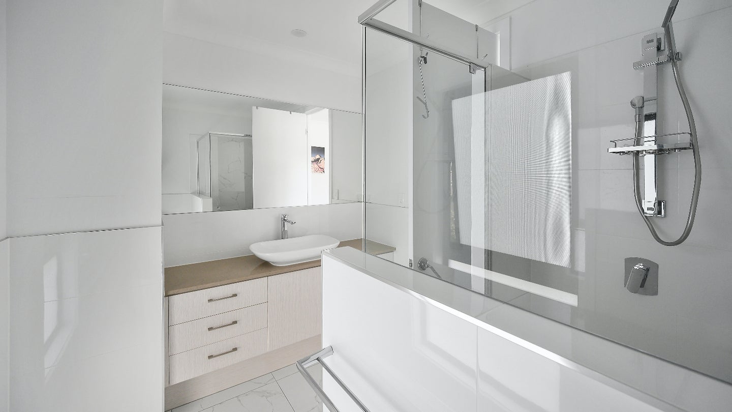 A white bathroom with chrome finishes and a light brown vanity.