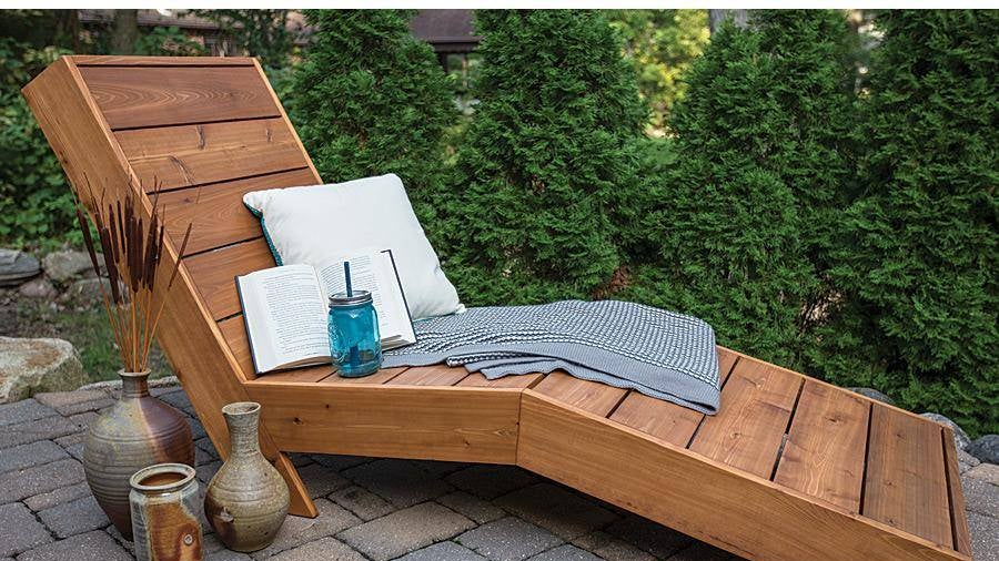 A wood chaise lounge sits on a brick patio.
