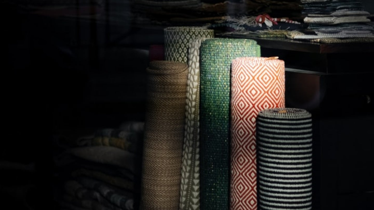 Rays of sunlight shining on a group of multicolored rolled-up carpets that are in a dark room.