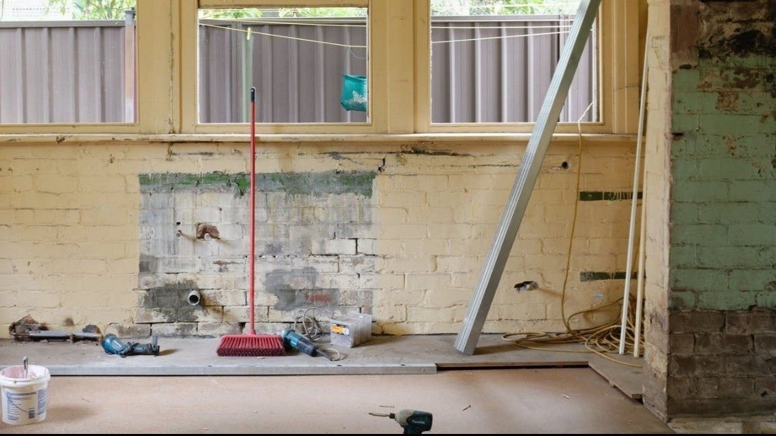 An unfinished area in a home with exposed brick, several windows, and a red broom with various tools on the floor.