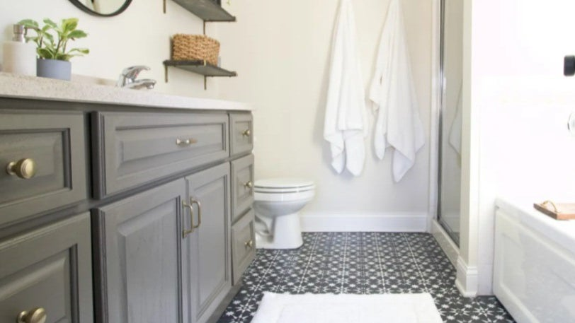 A bathroom with a gray vanity, a separate shower and bathtub, and black and white tiled floors.