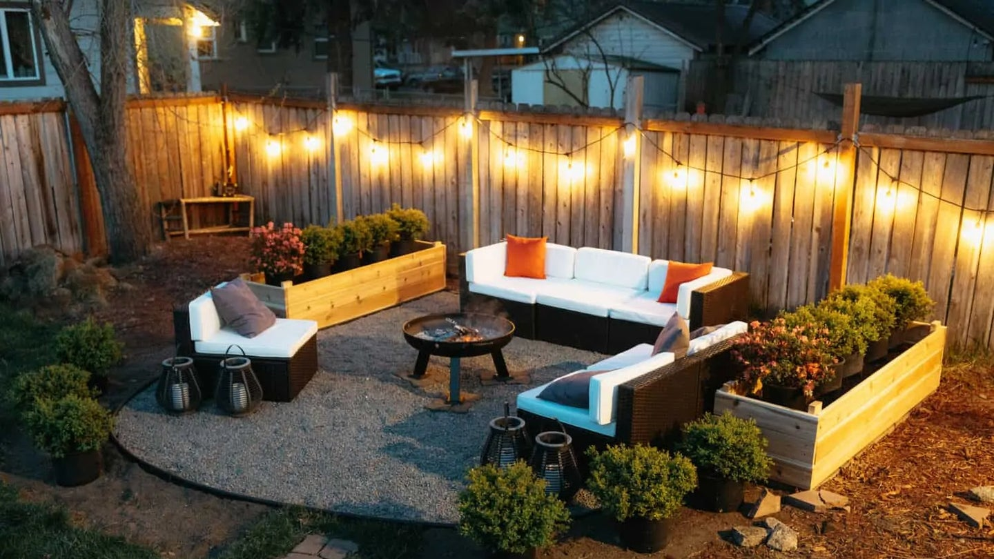 A backyard fire pit surrounded by couches and hanging lights.