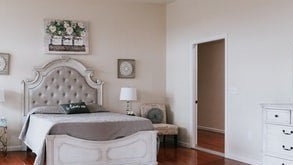 A white bedroom with a white and gray bed that has an antique headboard with a French pillow design.