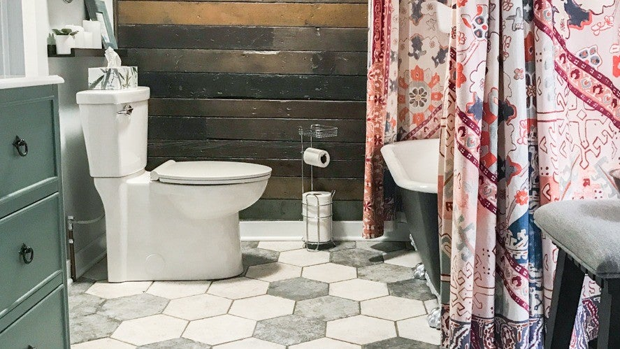 A bathroom with black and gray octagonal floor tiles, a wooden plank wall, and a pink floral designed shower curtain around the bathtub.