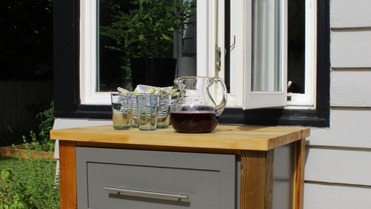A small kitchen cart with a butcher block top on an outdoor deck in front of a window.