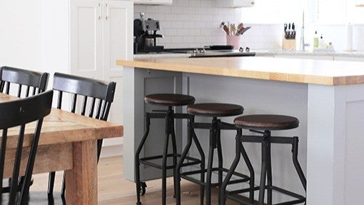 A white kitchen island with a butcher block countertop.
