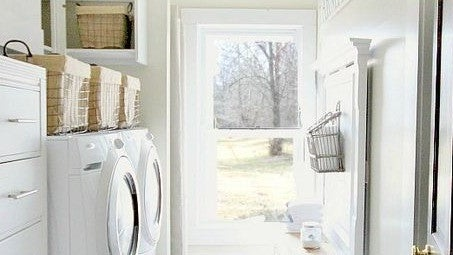 A laundry room with white appliances and lightly colored walls.