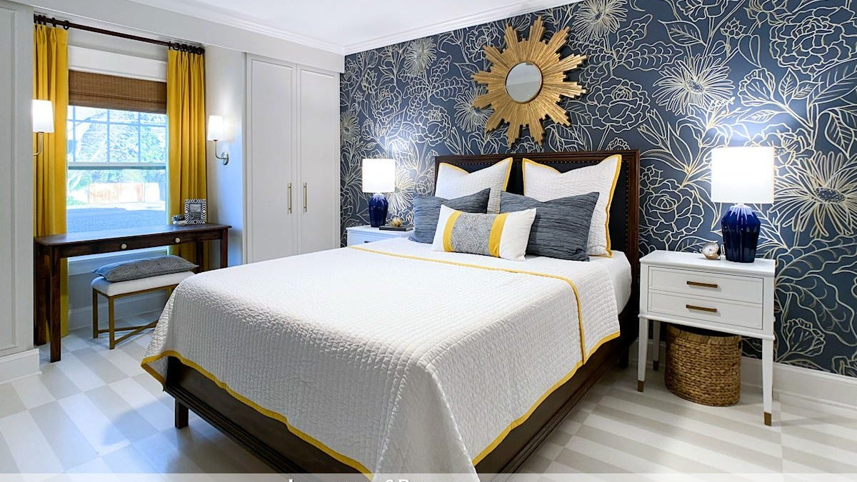 A bedroom with a navy blue accent wall that has gold floral designs painted all over it.