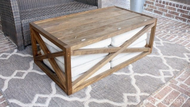 A wooden outdoor coffee table with cross designs and a hollow inside full of towels.