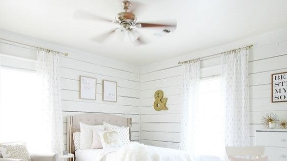 A white bedroom with white wooden planks all over the walls.