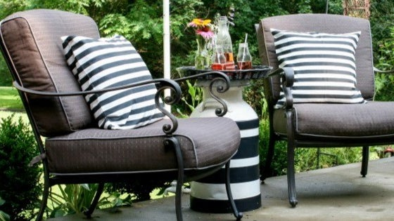 Two outdoor chairs surrounding a black and white striped side table made out of a tray and a large milk jug.