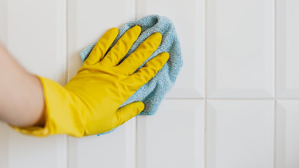 Crop person cleaning white tile wall with microfiber cloth.