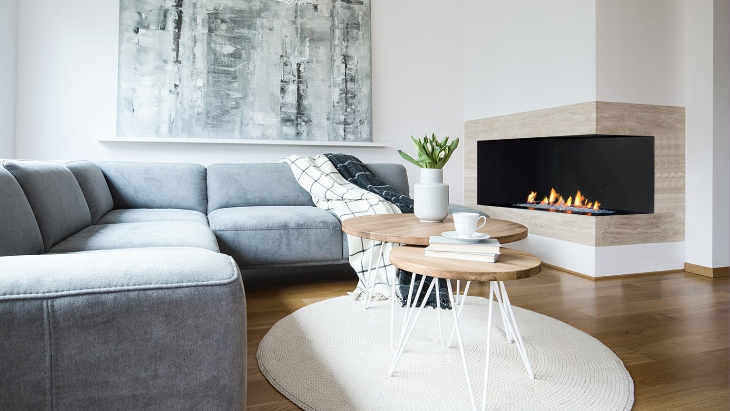 The corner fireplace meshes perfectly with the neutral tones of this chic living room
