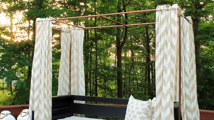 Copper cabana with chevron curtains surrounds a black and white daybed