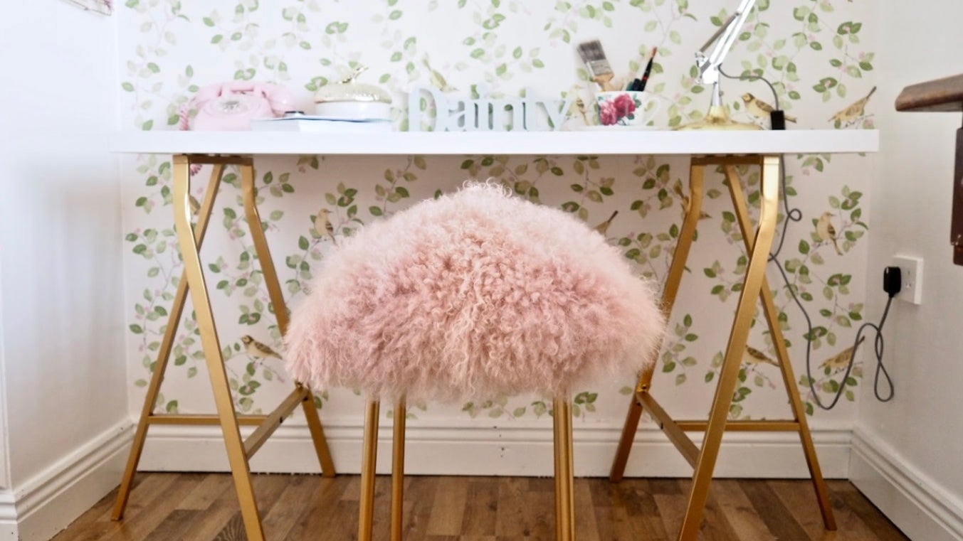 A fluffy pink and gold stool sits in front of a gold work desk