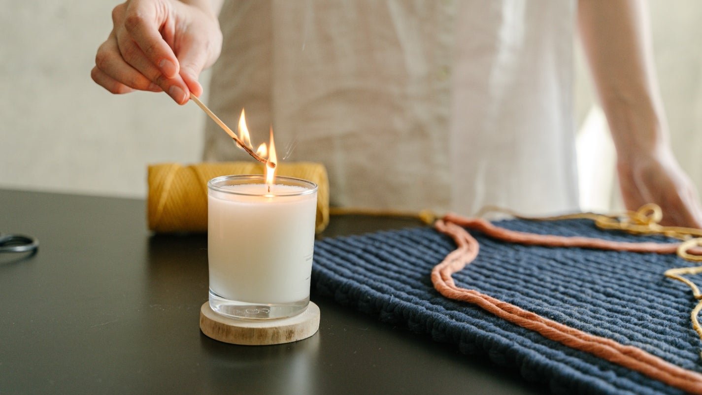 Person Holding White Candle on Black Wooden Table