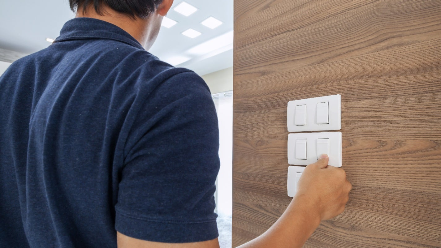 A man uses a light switch on a wood-trimmed wall.