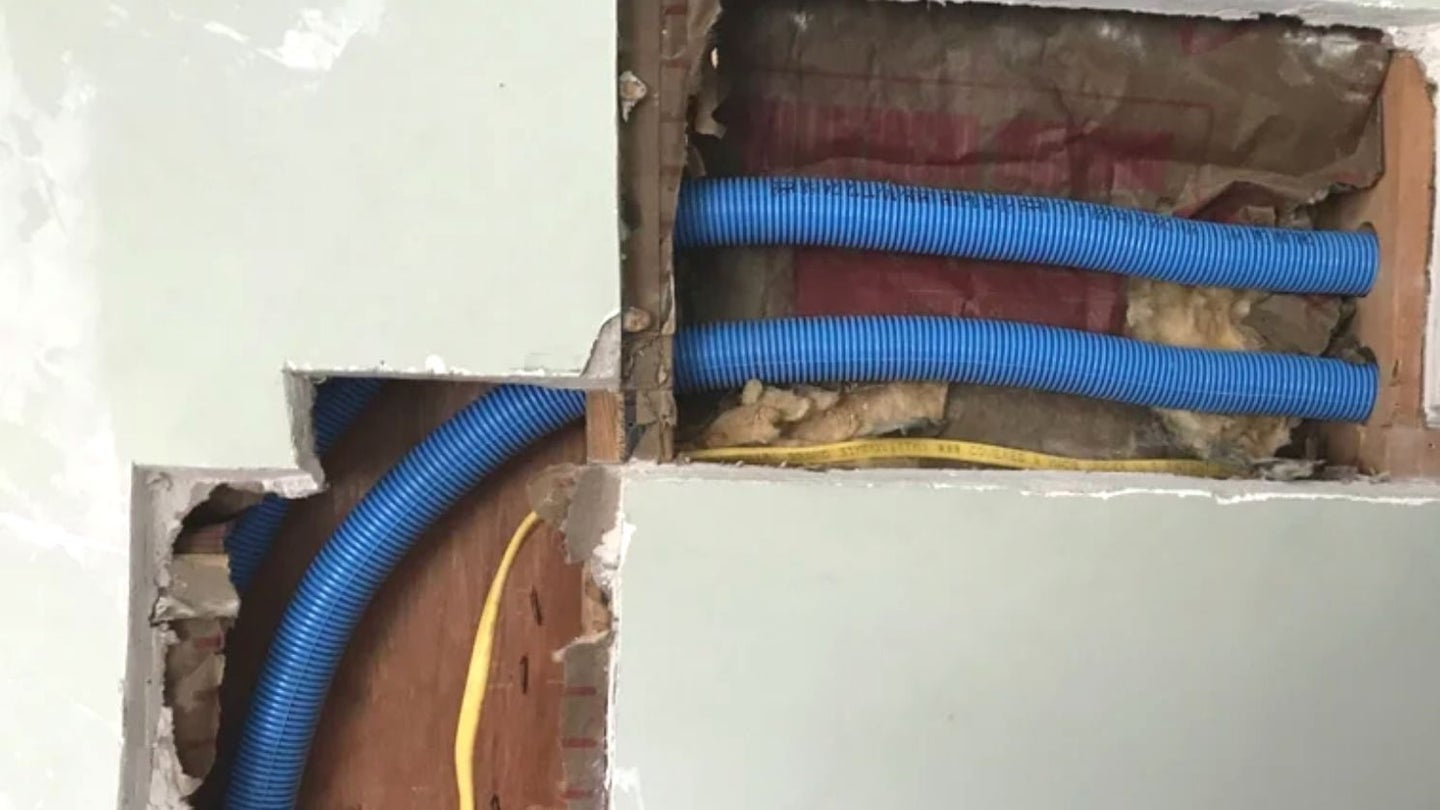 blue flexible electrical conduit running behind drywall that's been cut away.