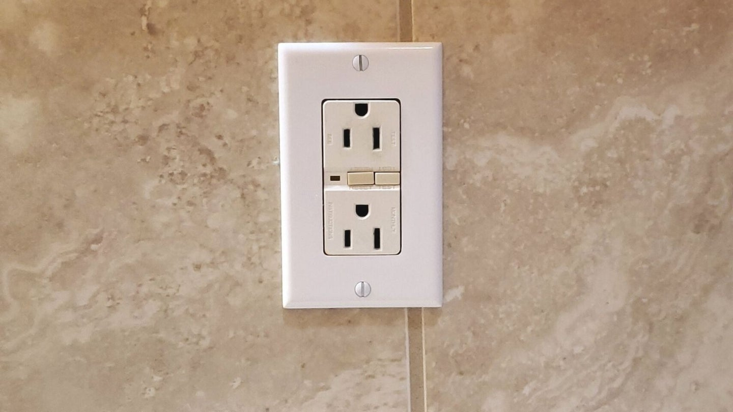 a gfci outlet in a bathroom on a tiled wall