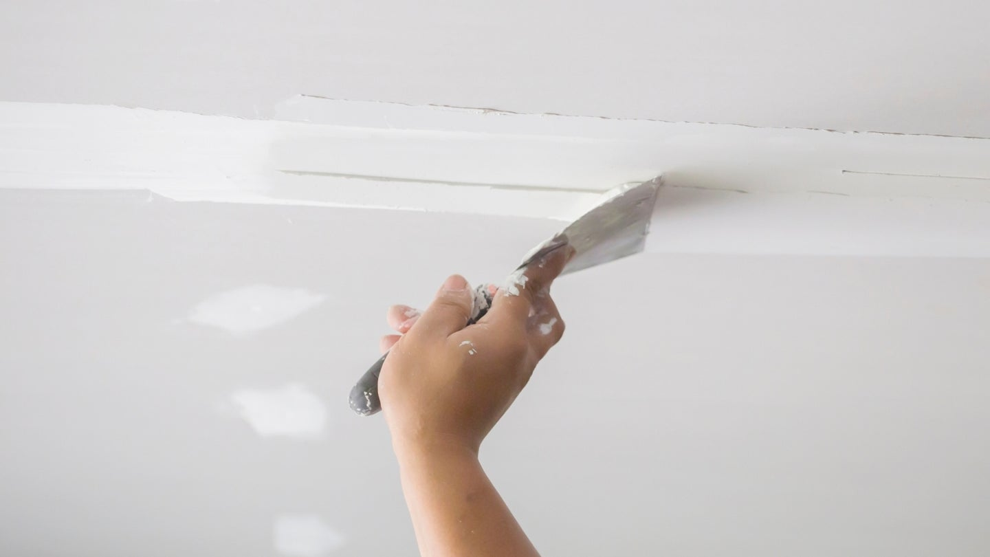 Hand holding putty knife mudding a horizontal crease on drywall